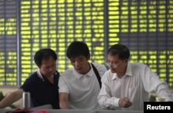 Sejumlah investor bercakap-cakap di di sebuah kantor pialang di Nantong, China (3/7).