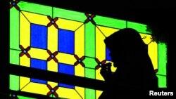 FILE - A Malaysian Muslim woman recites a prayer at a mosque in Kuala Lumpur.