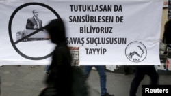 "FILE - A woman walks past a banner picturing Turkish President Recep Tayyip Erdogan that reads, ""When you arrest (journalists) or censor (media) we know that you are a war criminal, Tayyip,"" during a protest in Ankara, Turkey, Nov. 27, 2015."