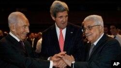 Menlu AS John Kerry (tengah) berjabat tangan dengan Presiden Israel Shimon Peres (kanan) dan Presiden Palestina, Mahmoud Abbas di sela-sela konferensi di Yordania (26/5).