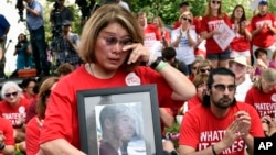 FILE - Maria Pike of Chicago, holding a photo of her son Ricky Pike, who was killed in 2012, attends a rally against gun violence on Capitol Hill in Washington, Sept. 10, 2015.