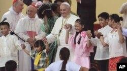 Paus Fransiskus menari dengan anak-anak Filipina pada kunjungan ke University of Santo Tomas di (18/1). (AP/Aaron Favila)