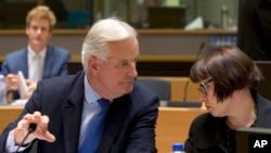 FILE - European Union chief Brexit negotiator Michel Barnier, left, speaks with EU Deputy Chief Negotiator Sabine Weyand during a meeting of EU General Affairs, Article 50, ministers in Brussels on Monday, Sept. 25, 2017.
