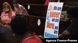 FILE - Activists wearing a rainbow mask sit at the Botswana High Court place placards as they listen to court proceeding, Oct. 12, 2021.