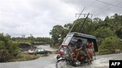 Cư dân Philippines lái xe chạy ngang qua một chiếc xe hơi bị cuốn trôi khỏi con đường bị ngập lụt tại thành phố Legazpi trong tỉnh Albay ở đông bắc Philippines