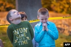 Green Community Church and Lutheran Church Charities of Roseburg, Ore., pray at a memorial in front of Snyder Hall on the campus of Umpqua Community College in Roseburg, Oct. 4, 2015.