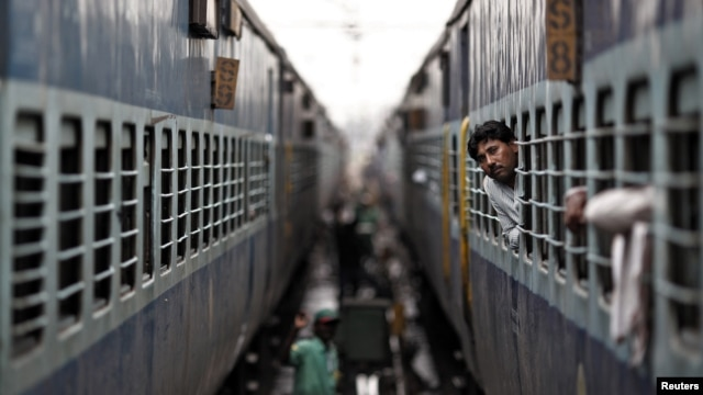 A passenger looks through the window of a stalled train as he waits for electricity to be restored at a railway station in New Delhi, India, July 31, 2012.