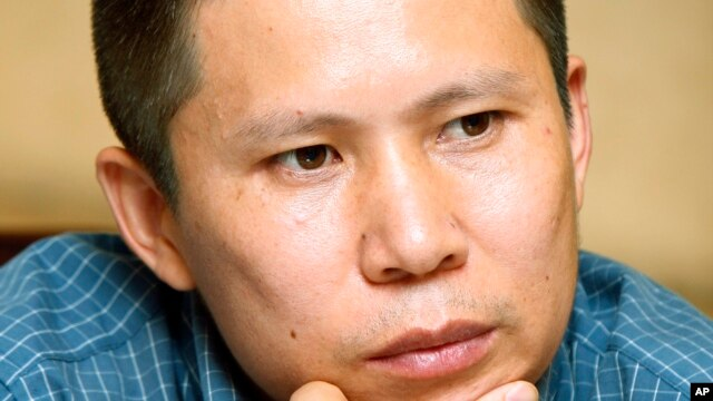 FILE - This July 17, 2009 file photo shows legal scholar Xu Zhiyong at a meeting in Beijing, China.