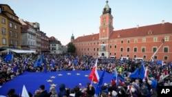 Para pengunjuk rasa tampak mengibarkan bendera Polandia dan Uni Eropa dalam aksi yang dilakukan untuk mendukung keanggotan Polandia di blok tersebut. Aksi tersebut dilakukan di Warsawa pada 10 Oktober 2021. (Foto: AP)