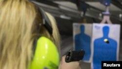 Seorang perempuan menembak di arena tembak di East Dundee, Ill., 21 April 2015.