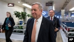 Sen. Dick Durbin, D-Illinois, followed by Sen. Bob Menendez, D-New Jersey, walks in the Capitol in Washington, Jan. 18, 2018.
