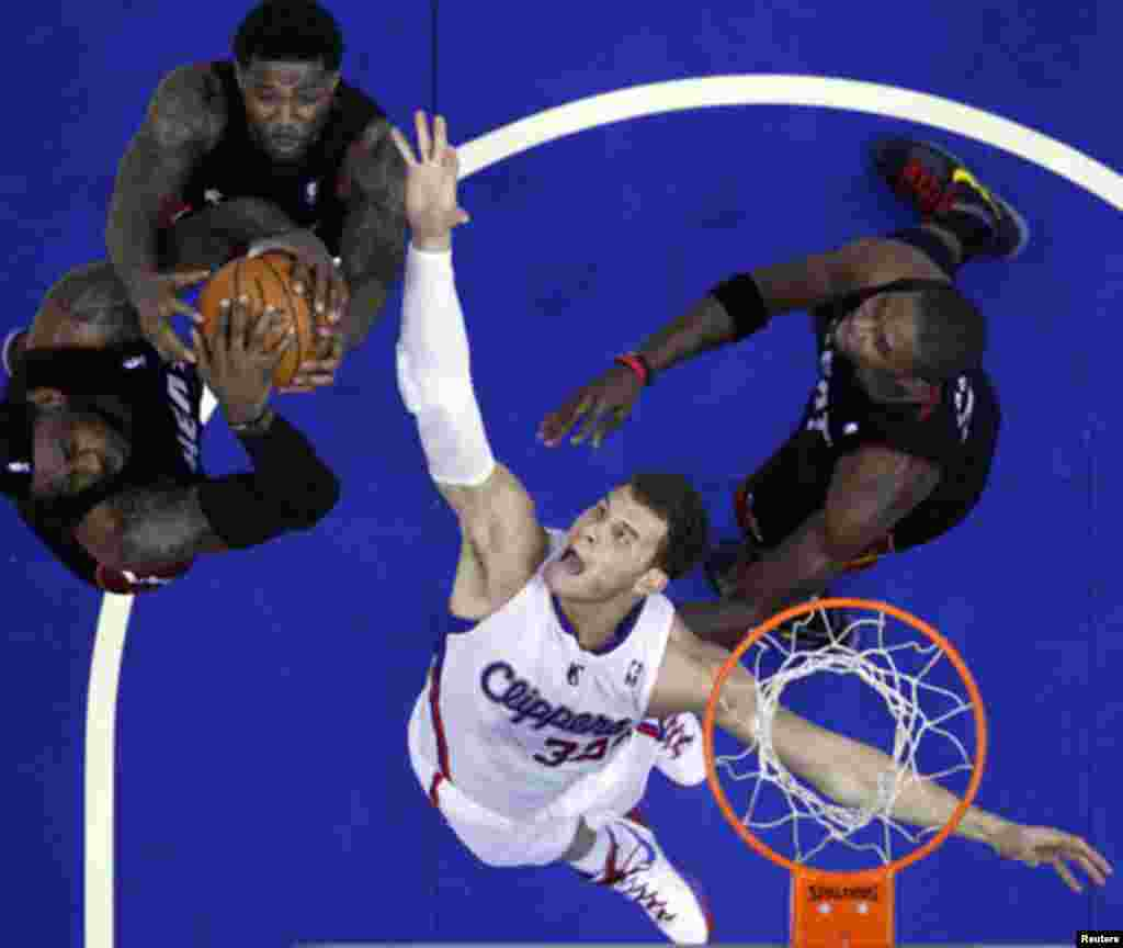 Los Angeles Clippers Blake Griffin (2nd R) fights for a rebound with Miami Heat's LeBron James (L-R), Udonis Haslem, and Chris Bosh during their NBA game in Los Angeles, California January 11, 2012.