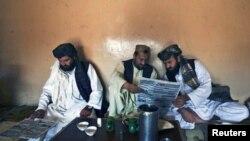 Pashtun men read local newspapers reporting the arrest of senior al Qaeda leader Younis al- Mauritani at roadside tea shop in Quetta.