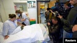 Y tá chuẩn bị ống tiêm vaccine ngừa virus Ebola cạnh một tình nguyện viên tại Bệnh viện Đại học Lausanne ở Lausanne, Thụy Sĩ, ngày 4/11/2014.