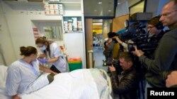 Une infirmière prépare une seringue contenant un vaccin expérimental à virus Ebola à côté d'un bénévole appelé Trina Helderman, à gauche, lors d'une visite de presse au Centre hospitalier universitaire vaudois à Lausanne, Suisse, le 4 novembre 2014.