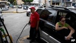 Archivo. En esta imagen del 23 de marzo de 2017 un empleado bombea gasolina para un cliente en una gasolinera en Caracas, Venezuela.