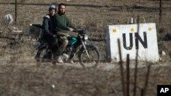 Archivo - En esta fotografía de noviembre de 2016, dos hombres conducen una moticicleta hacia una base abandonada de la ONU en la frontera de Quneitra entre Siria y los Altos del Golán.