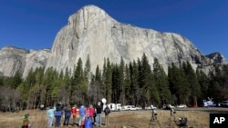Spectators look at El Capitan for a glimpse of climbers Tommy Caldwell and Kevin Jorgeson on Wednesday, Jan. 14, 2015, as seen from the valley floor in Yosemite National Park, Calif. Caldwell and Jorgeson became the first to free-climb the rock formation'