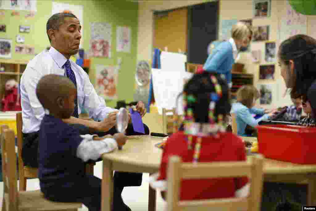 U.S. President Barack Obama reacts as he reads a card during a game with children in a per-kindergarten classroom at College Heights Early Childhood Learning Center in Decatur, Georgia.