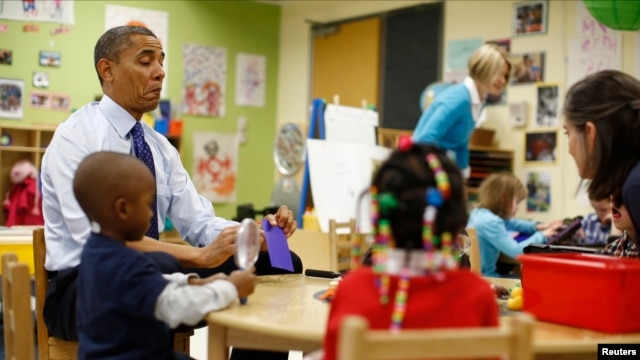U.S. President Barack Obama reads a card during a game with children in a per-kindergarten classroom at College Heights early childhood learning center in Decatur, Georgia, February 14, 2013.
