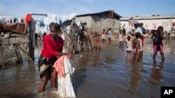 一名海地妇女在洪水造成的积水中洗衣物和床被。(2014年11月4日)