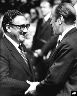 រូបឯកសារ៖ លោកប្រធានាធិបតី Gerald Ford និងលោករដ្ឋមន្ត្រីការបរទេស Henry Kissinger ចាប់ដៃនៅសេតវិមានកាលពីថ្ងៃទី១៥ ខែឧសភា ឆ្នាំ១៩៧៥។ មុននេះលោកប្រធានាធិបតីបានប្រកាសថា កងម៉ារីនរបស់អាមេរិកបានរកឃើញកប៉ាល Mayaguez និងមនុស្ស៤០នាក់នៅក្បែរកោះតាង។ (រូបថត AP)