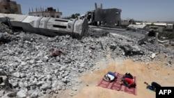Gazze'de yıkılmış bir caminin yanında namaz kılan Filistinliler