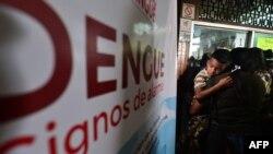 ہنڈورس میں ایک خاتون بخار میں مبتلا اپنے بچے کو علاج کے لیے ڈینگی سے بچاؤ کے مرکز میں لا رہی ہے۔