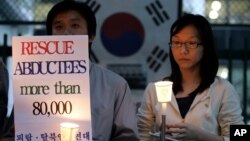 FILE - Members of the Korean Abductees to North Korea, the supporting group for those abducted by North Korea at the 1950-53 Korean War, participate at an anti-Koreas Summit candle rally in front of the government house in Seoul, South Korea, Oct. 2, 2007.