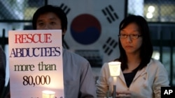 FILE - Members of the Korean Abductees to North Korea, the supporting group for those abducted by North Korea at the 1950-53 Korean War, participate at an anti-Koreas Summit candle rally in front of the government house in Seoul, South Korea, Oct. 2, 2007