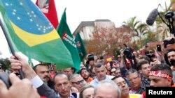 Luiz Inacio Lula da Silva avèk yon drapo Brezilyen nan men li pandan li t ap antre nan yon tribinal pou l fè depozisyon li nan vil Curitiba, Brezil, nan dat 10 me 2017.