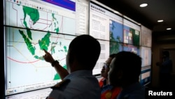 Military and rescue authorities monitor progress in the search for AirAsia Flight QZ8501 inside the National Search and Rescue Agency, Jakarta, Dec. 29, 2014.