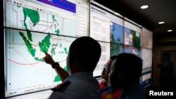 Military and rescue authorities monitor progress in the search for AirAsia Flight 8501 inside the National Search and Rescue Agency in Jakarta, Indonesia, Dec. 29, 2014.