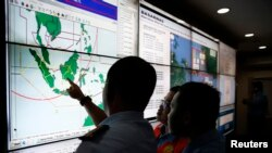 Military and rescue authorities monitor progress in the search for AirAsia Flight QZ8501 inside the National Search and Rescue Agency in Jakarta, December 29, 2014.
