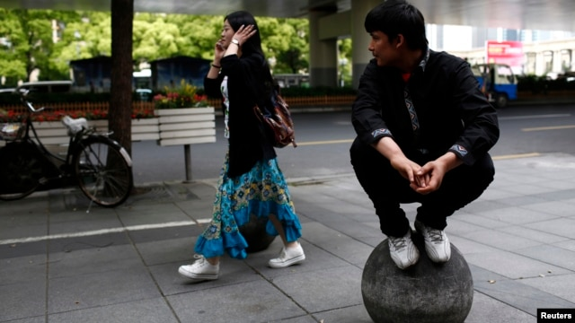 FILE - A Uighur man looks at a passing Han woman outside of his restaurant in Shanghai, April 23, 2014.