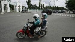 Perempuan Aceh naik sepeda motor di Banda Aceh, sesuatu yang hampir dilarang oleh pemerintah Lhokseumawe karena dianggap tidak pantas. (Reuters/Junaidi Hanafiah)
