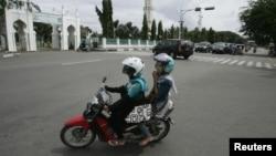 Dua perempuan Aceh berboncengan di atas sepeda motor dekat Mesjid Baiturrahman di Banda Aceh (3/1). (Reuters/Junaidi Hanafiah)