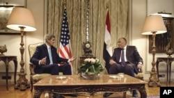 Menteri Luar Negeri AS John Kerry, kiri, berbicara dengan Menteri Luar Negeri Mesir Sameh Shoukry, sebelum rapat di Kementerian Luar Negeri di Kairo, Mesir, Minggu, 2 Agustus 2015. (Brendan Smialowski/Pool Photo via AP)