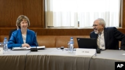 Kepala urusan kebijakan luar negeri Uni Eropa Catherine Ashton (kiri) bersama Menlu Iran Javad Zarif sesaat sebelum dimulainya dialog nuklir di Jenewa (15/10).