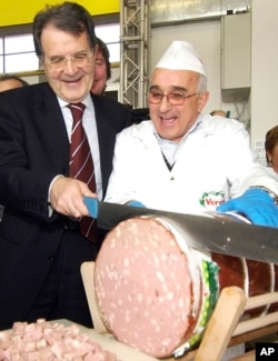 Romano Prodi slices a large Italian sausage while running for office in Bologna, Italy in 2006.