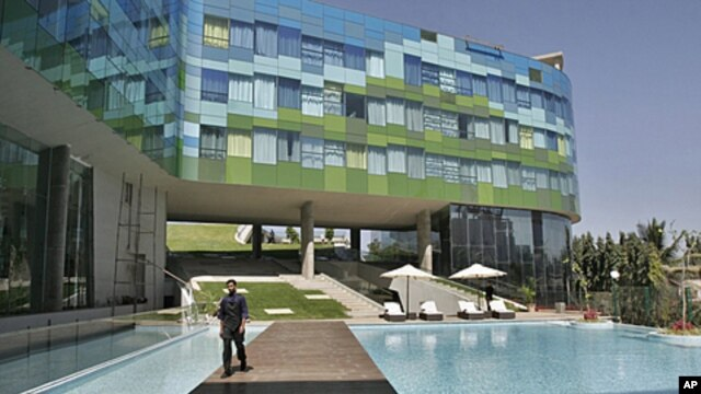 A staff member of Vivanta By Taj, a Tata group hotel, walks past the swimming pool at a luxury hotel in Bangalore, India. People in cities like Jaipur want international experiences similar to the kind available in big cities. (2009 File)