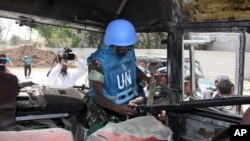A U.N. observer takes pictures of a military bus that was damaged by a roadside bomb, at al-Bahdaliyah area, near Damascus, Syria, Wednesday, May 23, 2012.