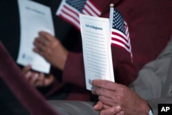 "FILE - Participants hold the ""Oath of Allegiance"" and American flags during a naturalization ceremony at the National Archives in Washington, Dec. 15, 2015."