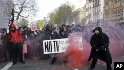 Protesters in London set off a smoke flare as thousands of students across Britain protest against tuition fee hikes, 24 November 2010