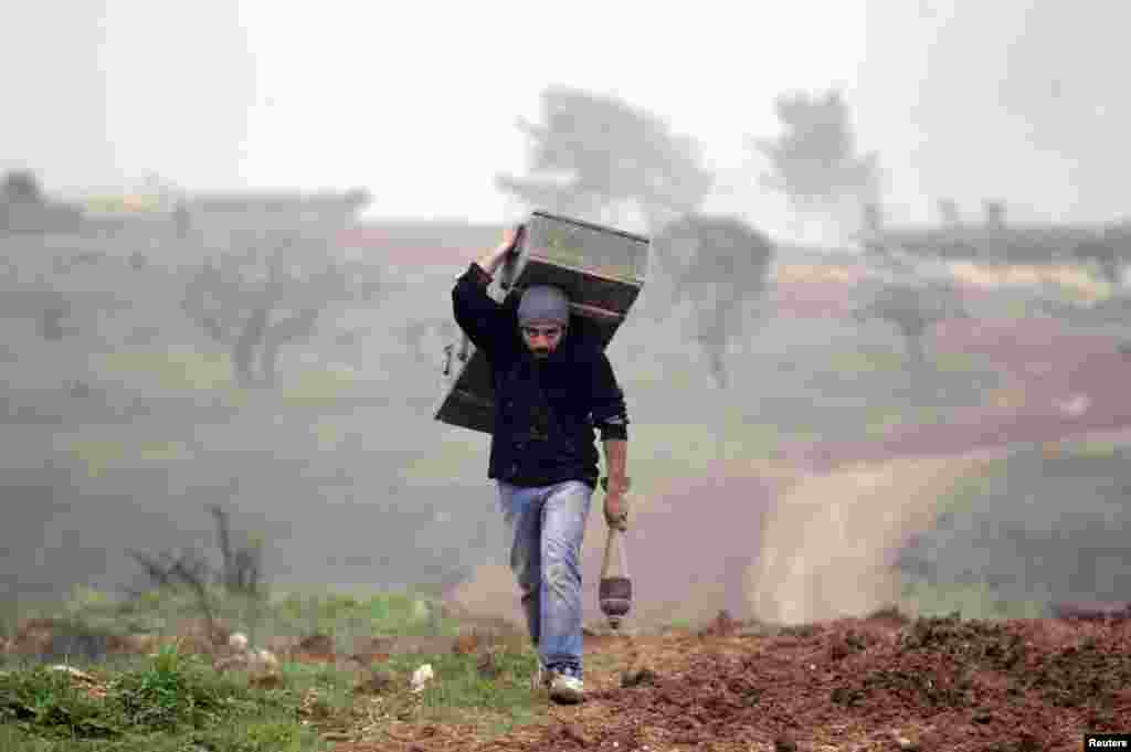 A man carries a weapon box left behind by forces loyal to Syria's President Bashar al-Assad at the Azaalana checkpoint in the southern Idlib countryside, Dec. 20, 2014.