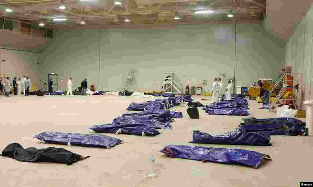 Body bags containing African migrants, who drowned trying to reach Italian shores, lie in a hangar of the Lampedusa airport, Italy, Oct. 3, 2013.