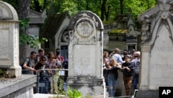 Fans gather at the tomb of rock singer Jim Morrison at the Pere-Lachaise cemetery in Paris, July 3, 2021.