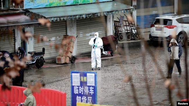Një punonjës me kostum mbrojtës, në një treg të mbyllur peshku në fillim të pandemisë në Wuhan, Kinë.
