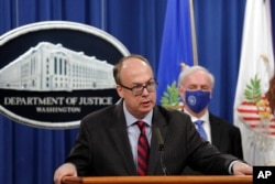 FILE - Acting Assistant U.S. Attorney General Jeffrey Clark speaks as he stands next to Deputy Attorney General Jeffrey Rosen during a news conference at the Justice Department in Washington, Oct. 21, 2020.