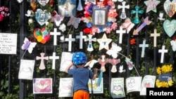"""在紐約布魯克林區的綠木公墓(Green-Wood Cemetery),一個孩子在觀看""""寫下逝者名字紀念牆""""(""""Naming the Lost Memorials"""" )。(2021年6月10日)"""